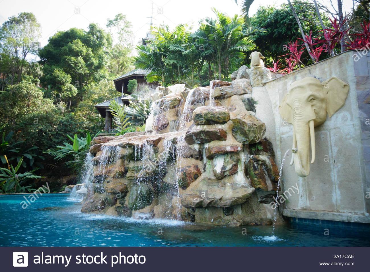 Beautiful turquoise swimming pool with waterfall rocks ...