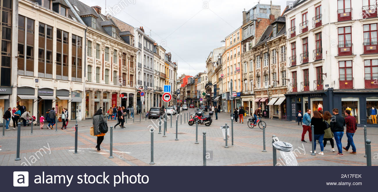 LILLE, FRANCE - APRIL 15, 2017: Shopping and sightseeing people along the Rue Esquermoise and Place du General de Gaulle with shops. The street and th Stock Photo