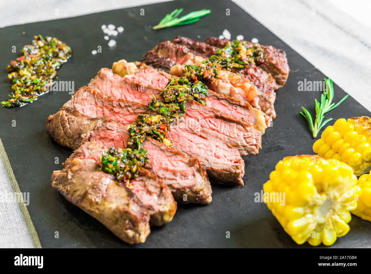 Sliced medium rib eye beef steak meat with chimichurri on black background Stock Photo