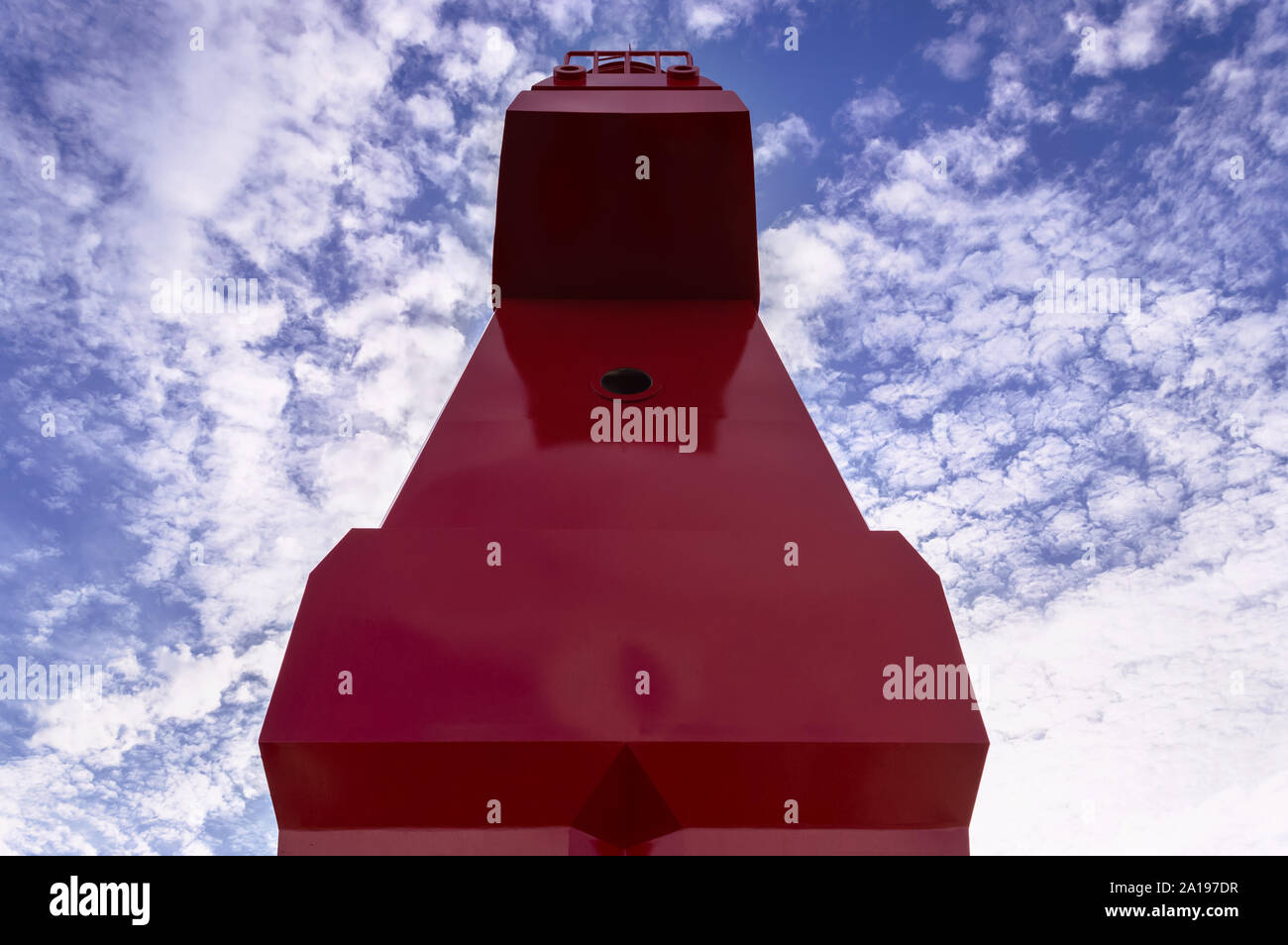 close up view of red horse shaped lighthouse against scenic cloudscape on Jeju island - Stock Photo