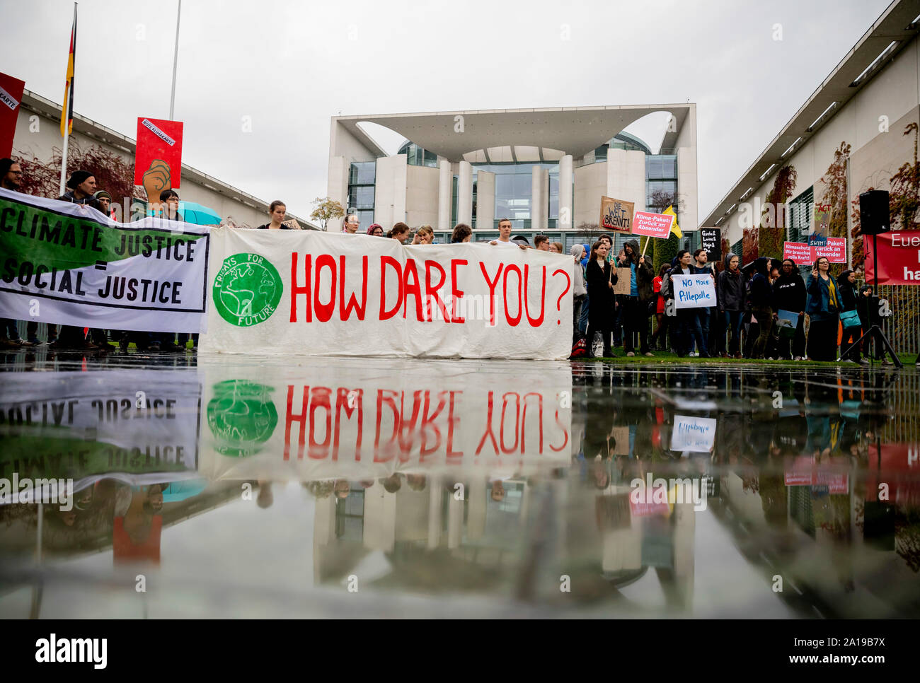 """Berlin, Germany. 25th Sep, 2019. """"How dare you?"""" (How dare you?) can be read on a banner in front of the Federal Chancellery at a rally of Fridays for Future and the non-governmental organisation Campact against the climate policy of the Federal Government. Credit: Christoph Soeder/dpa/Alamy Live News Stock Photo"""