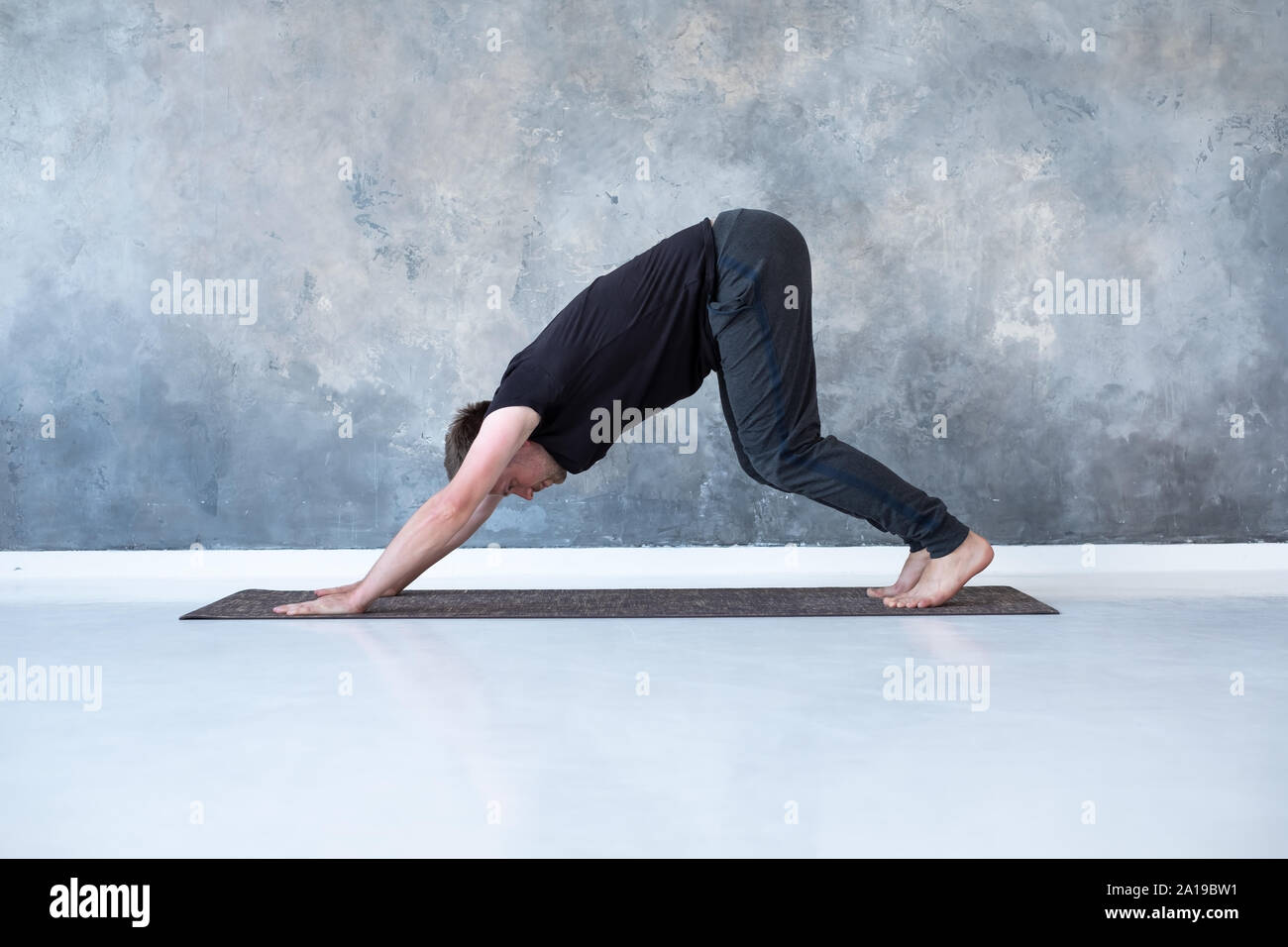 Young man working out, standing in yoga downward facing dog pose
