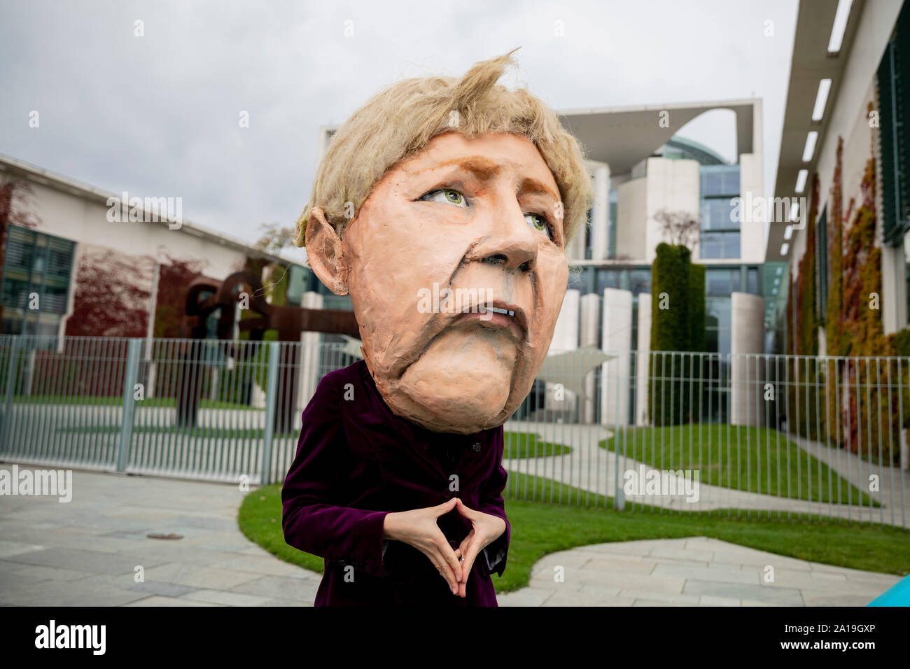 Berlin, Germany. 25th Sep, 2019. At a rally of Fridays for Future and the non-governmental organisation Campact against the climate policy of the Federal Government, one actress wears a mask in front of the Federal Chancellery which Chancellor Angela Merkel (CDU) shows. Credit: Christoph Soeder/dpa/Alamy Live News Stock Photo