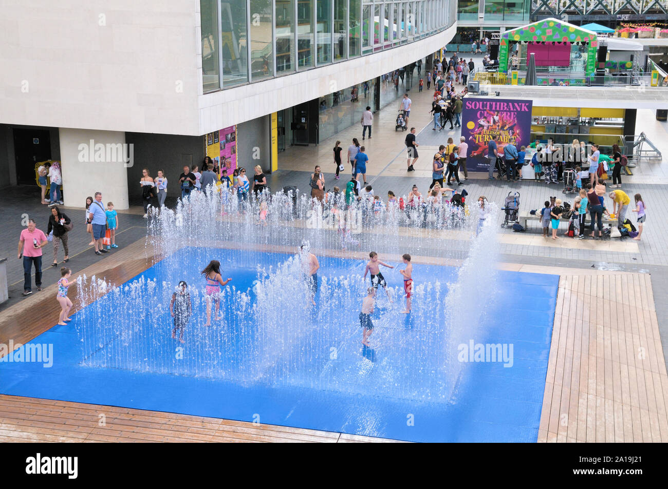 Children having fun playing in the water jet fountains in the Appearing Rooms installation by Danish artist Jeppe Hein, Southbank Centre, London, UK Stock Photo