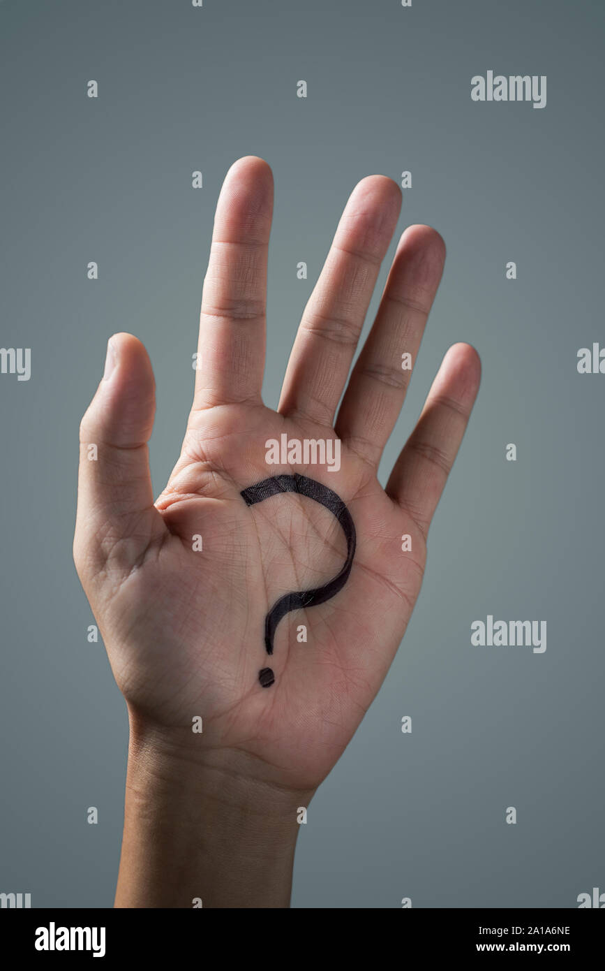 man with a question mark painted in the palm of his hand on an off-white background Stock Photo