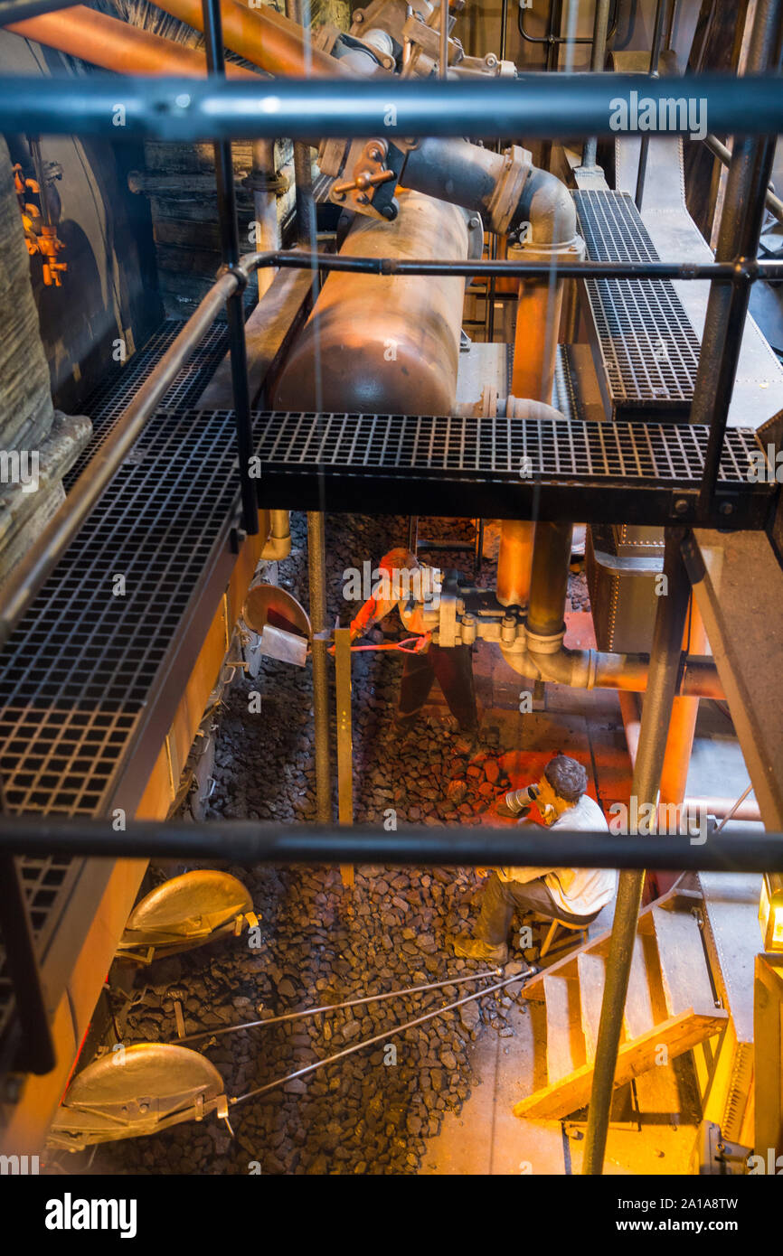 Re-created Engine room and furnace being fed coal by mannequin model figures; engine of the SS Great Britain, Brunel's steam powered ship in dry dock in in Bristol. UK England (109) Stock Photo