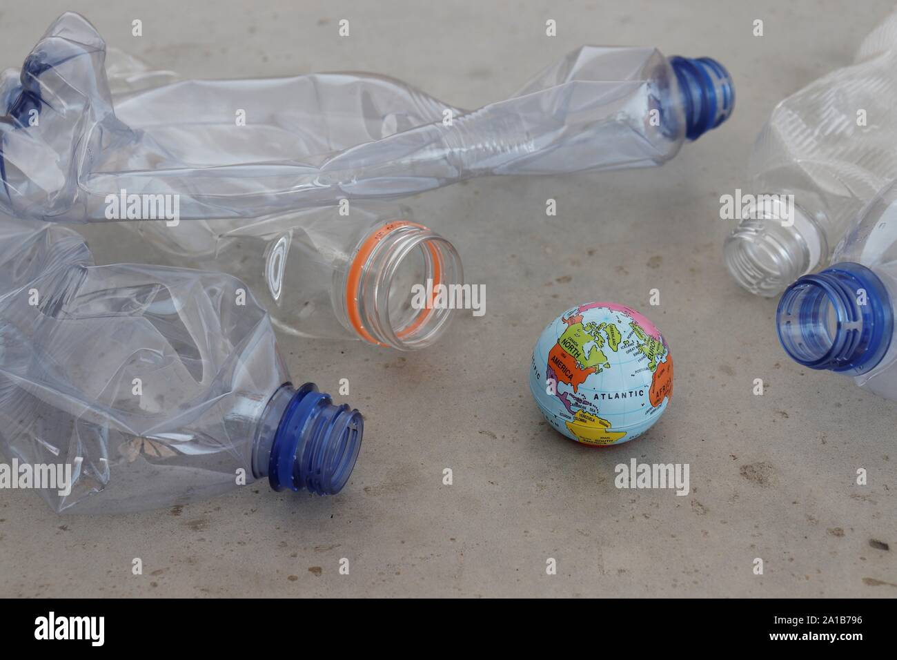 Pet plastic bottles pointing at planet earth globe on grey surface. Showing plastic pollution, recycling and zero waste concepts. Stock Photo