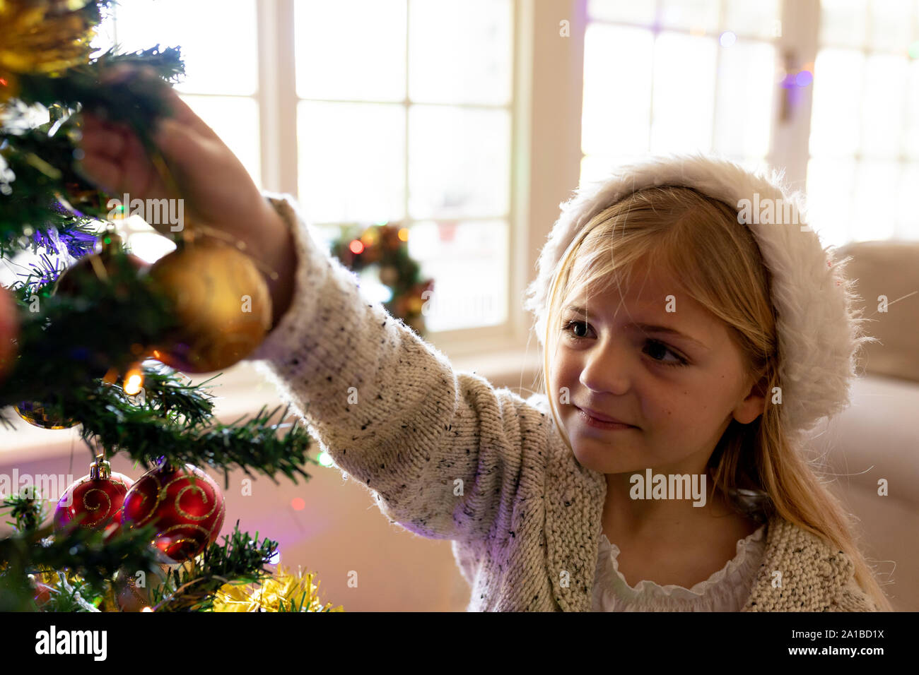 Girl decorating tree at Christmas time Stock Photo