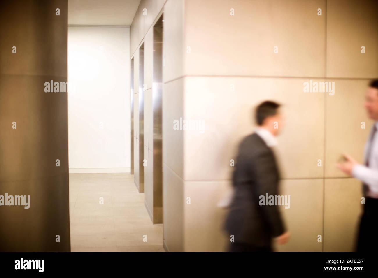 Businessmen walking by an elevator lobby. Stock Photo