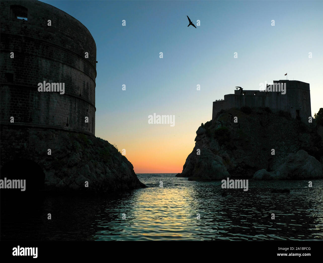 A view out to the Adriatic sea from the Old Town of Dubrovnik at sunset. The view shows the city walls with Alpine Swifts in flight in the sky Stock Photo