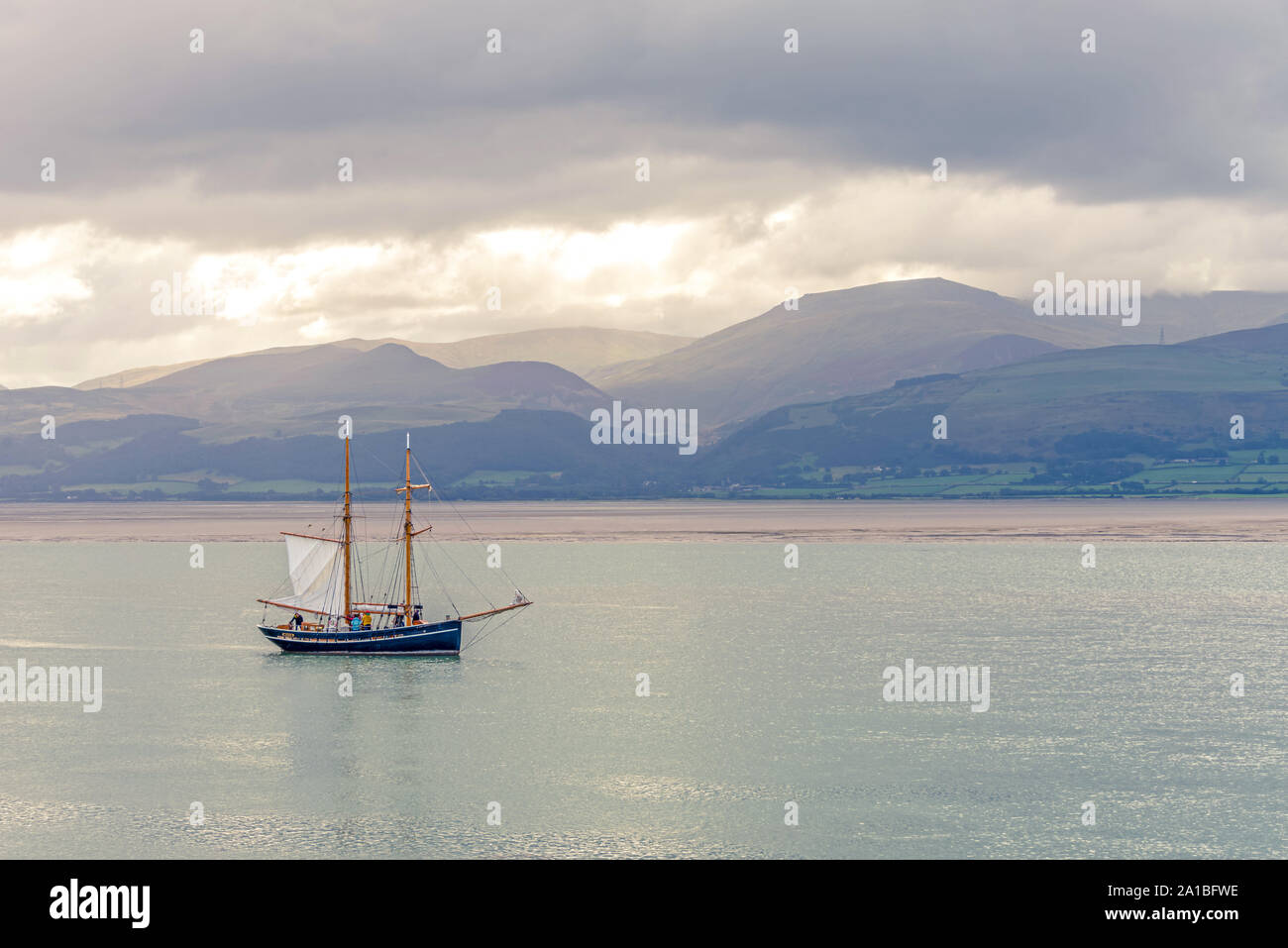 The Menai Strait at Beaumaris.  A sailing ship manoeuvres against a backdrops of cloud topped hills. Stock Photo
