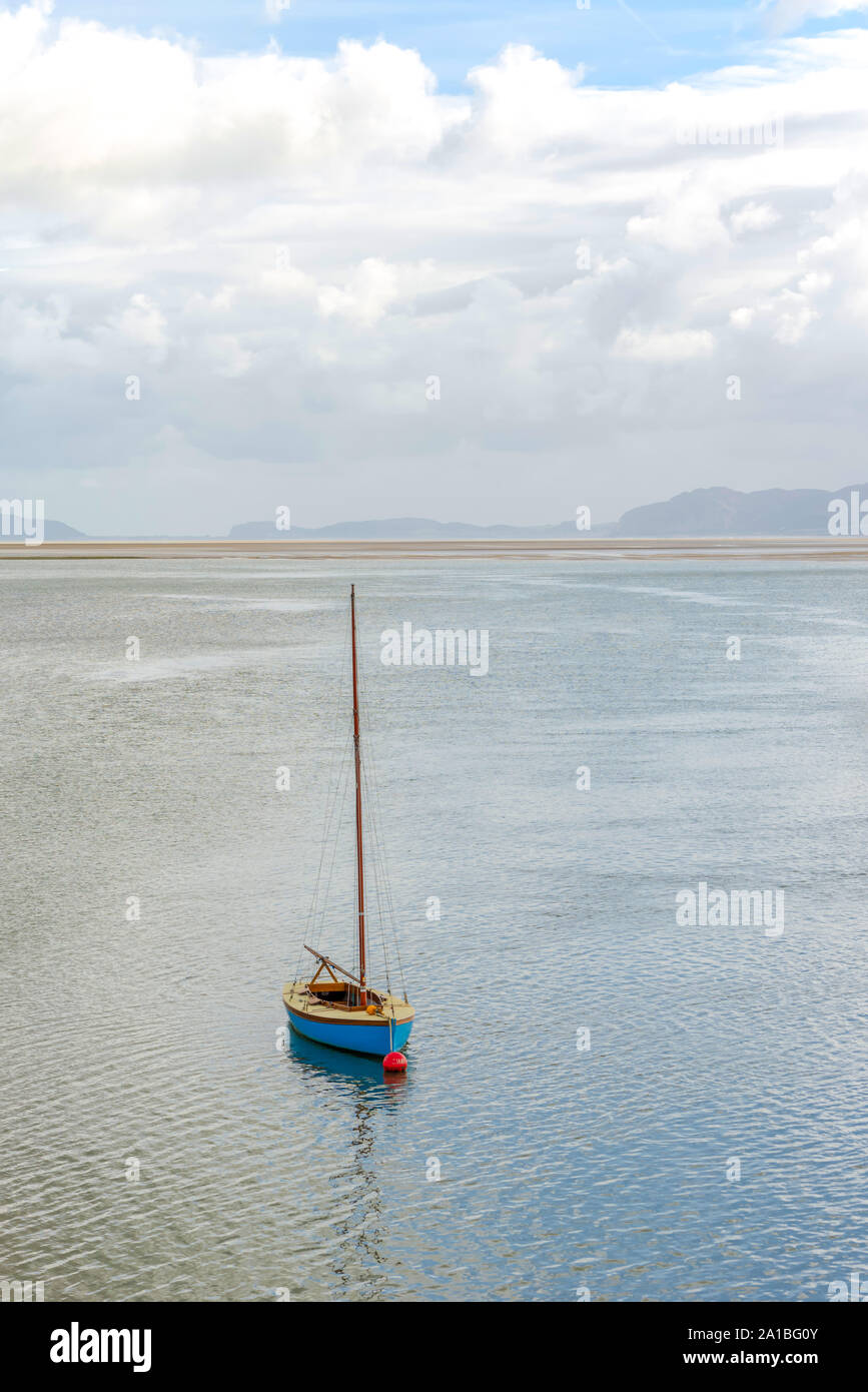 The Menai Strait at Beaumaris.  Boats are moored near the land with a yacht in the foreground.  A heavy cloud is above. Stock Photo