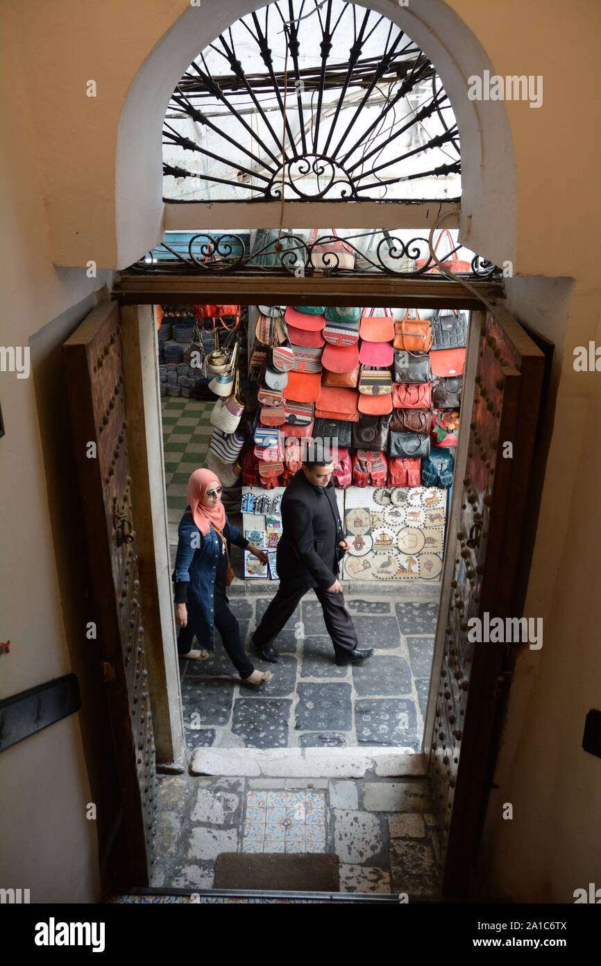 Looking out the front door of a home onto a pedestrian alleyway with people walking in the medina (old city) of Tunis, Tunisia. Stock Photo