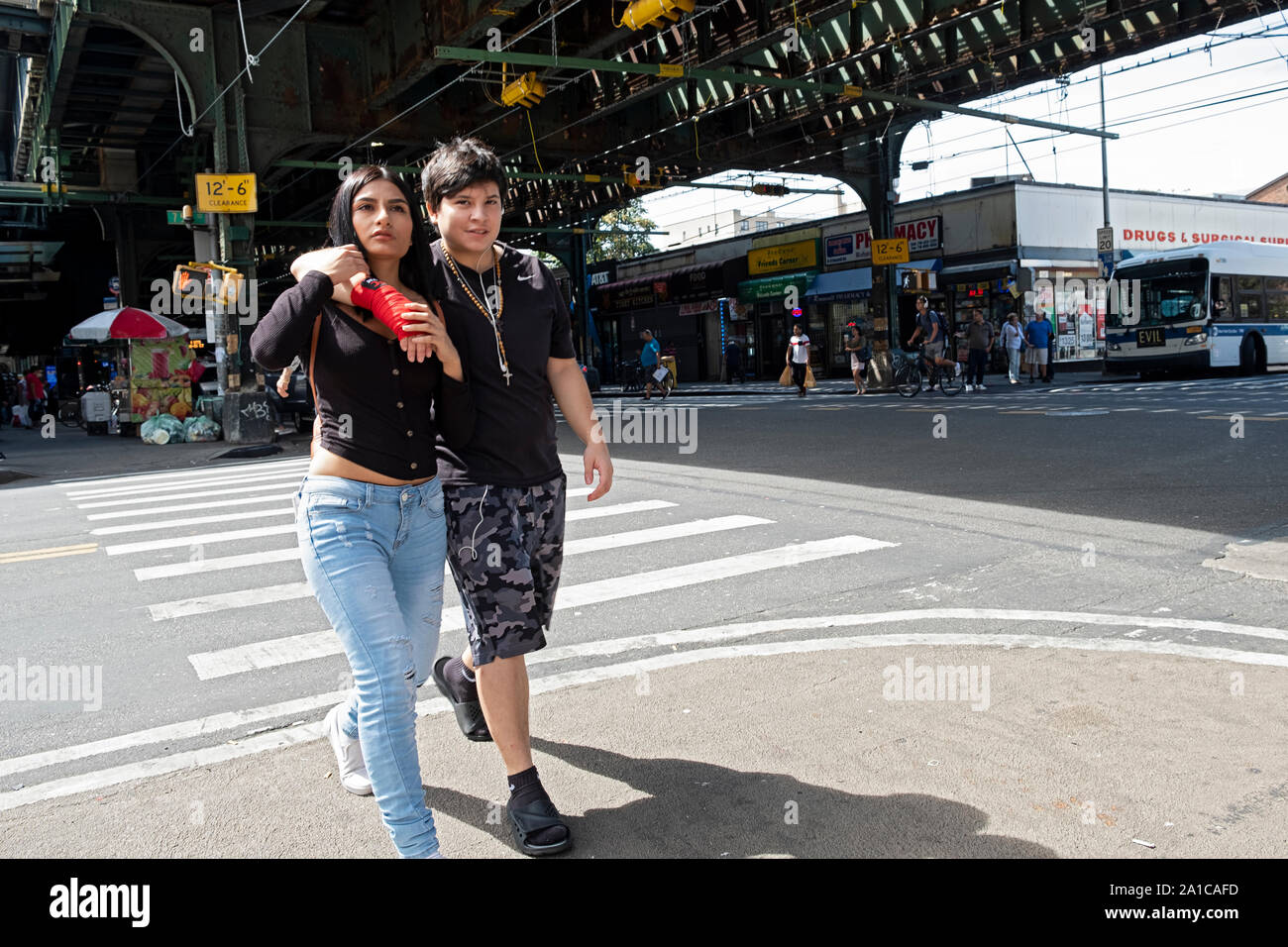 A young couple, likely South American, walk together under the elevated subway in Jackson Heights, Queens, New York City, Stock Photo