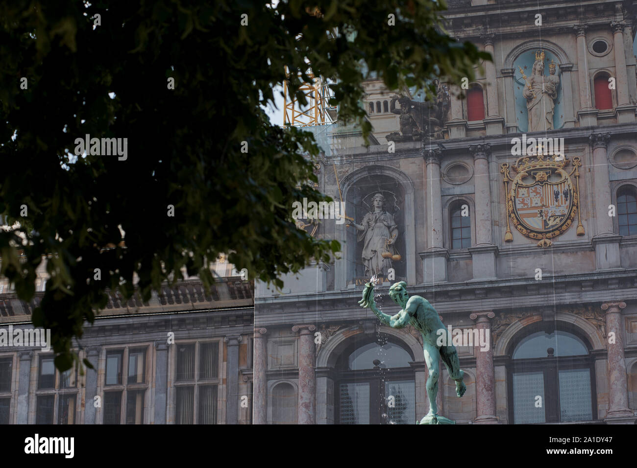 Statue of Silvius Brabo, slayer of Druon Antigoon, in the Grote Markt with the Antwerp City Hall (Antwerpen Stadhuis) in the background. Stock Photo