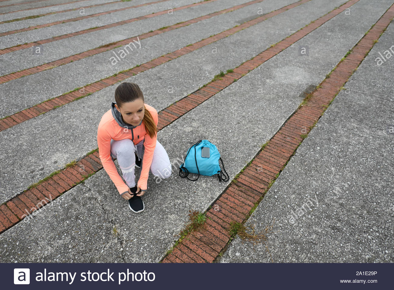 Young female athlete getting ready for outdoor running workout. Sporty girl lacing footwear outside. Stock Photo