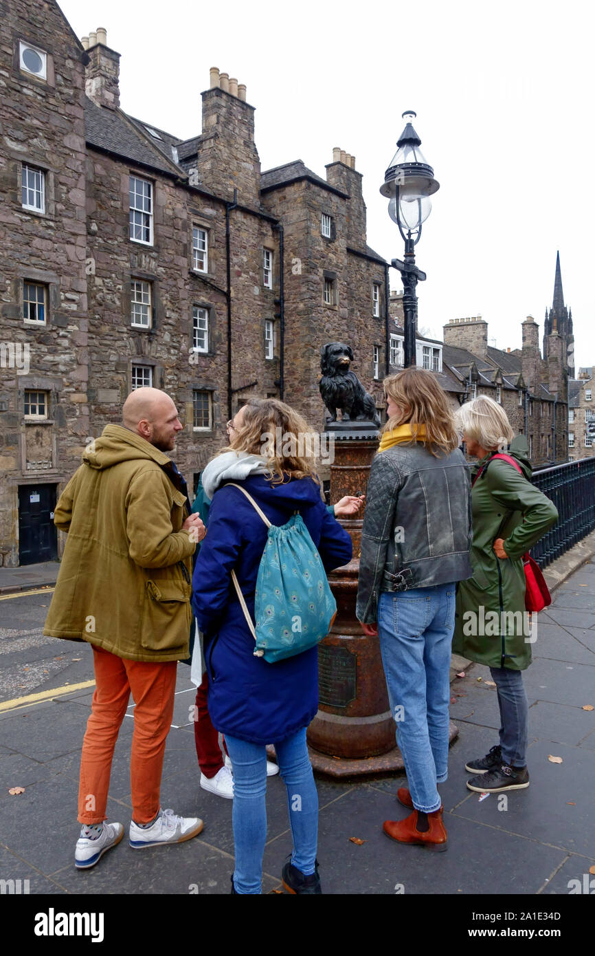 Tourists looking at the Greyfriars Bobby statue at the corner of Candlemaker Row and George IV Bridge in Edinburgh, Scotland Stock Photo