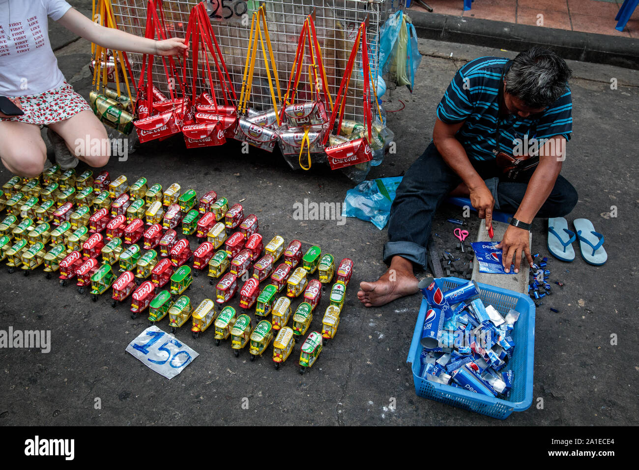 BANGKOK, THAILAND: A street vendor sits on the ground as he makes Tuk Tuk models out of soft drink cans on Khao San Road in Bangkok, Thailand on August 22nd, 2019. Bangkok's bustling Khao San Road - a strip famous among tourists for its budget hostels, street food and market stalls - is set for a £1.28M face lift in October this year.   For many backpackers Khao San is the starting point for their travels across Southeast Asia. It is a place to meet fellow travellers, dine out on pad thai served from street carts, sip cocktails from small brightly-coloured buckets or perhaps get an ill-advised Stock Photo