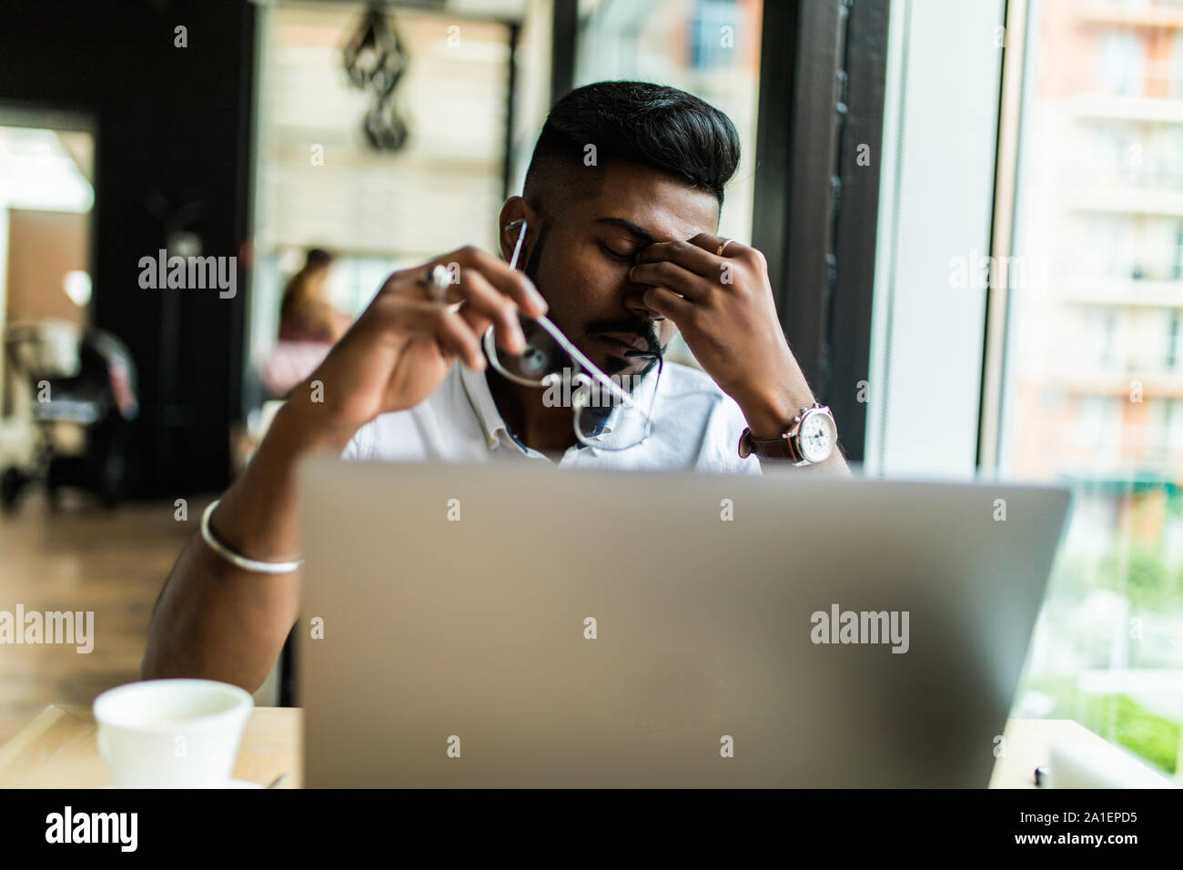 Young Asian businessman suffering from tired eyes after long hours of using laptop. Stock Photo