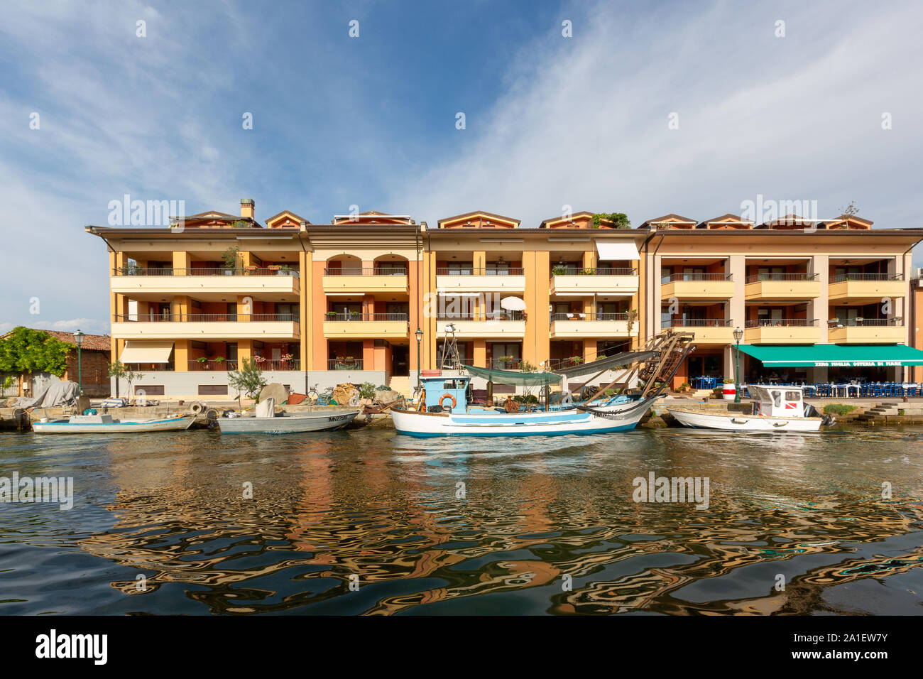 JULY 22, 2019 - GRADO, ITALY - Colored residential buildings and boats in the sunset light are mirror reflected in sea water of the harbor of Grado Stock Photo