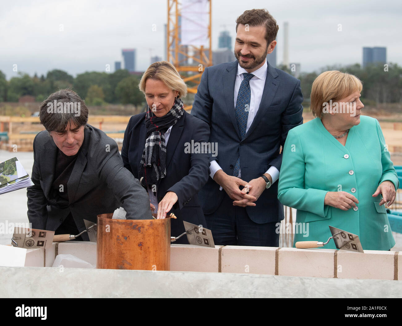 26 September 2019, Hessen, Frankfurt/Main: Federal coach Joachim Löw (l-r), DFB trainer Martina Voss-Tecklenburg, Friedrich Curtius, DFB Secretary General and Federal Chancellor Agela Merkel (CDU) jointly equip a time capsule at the laying of the foundation stone of the DFB Academy. Photo: Boris Roessler/dpa Stock Photo
