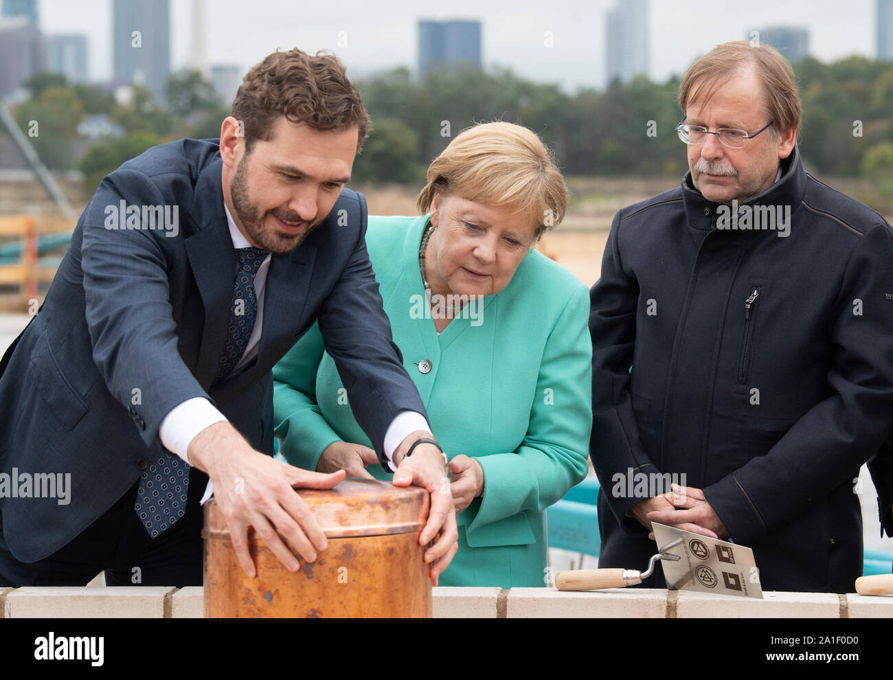 26 September 2019, Hessen, Frankfurt/Main: Friedrich Curtius (l-r), DFB Secretary General, Federal Chancellor Agela Merkel (CDU) and Rainer Koch, DFB Interim President, jointly equip a time capsule at the laying of the foundation stone for the DFB Academy. Photo: Boris Roessler/dpa Stock Photo