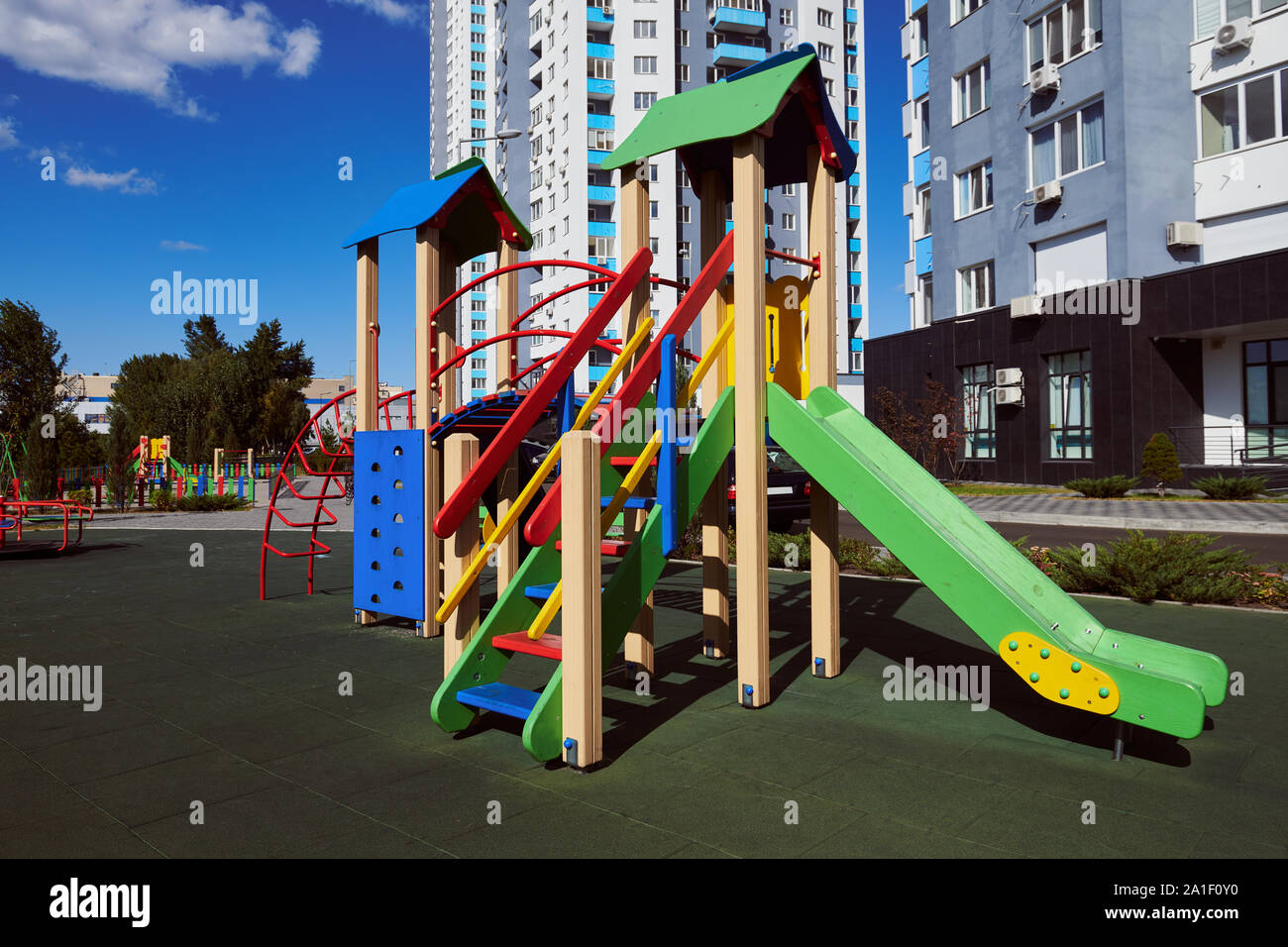 Empty colorful wooden children's slide with ladder on the playground. Attraction located in the yard against high-rise building and blue sky. Stock Photo