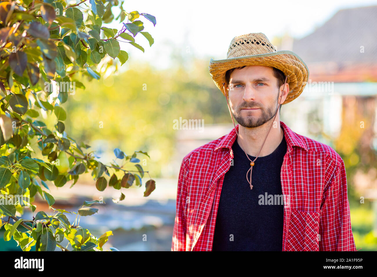 Handsome cowboy, portrait of a farmer in his garden. A man in a cowboy hat. Stock Photo