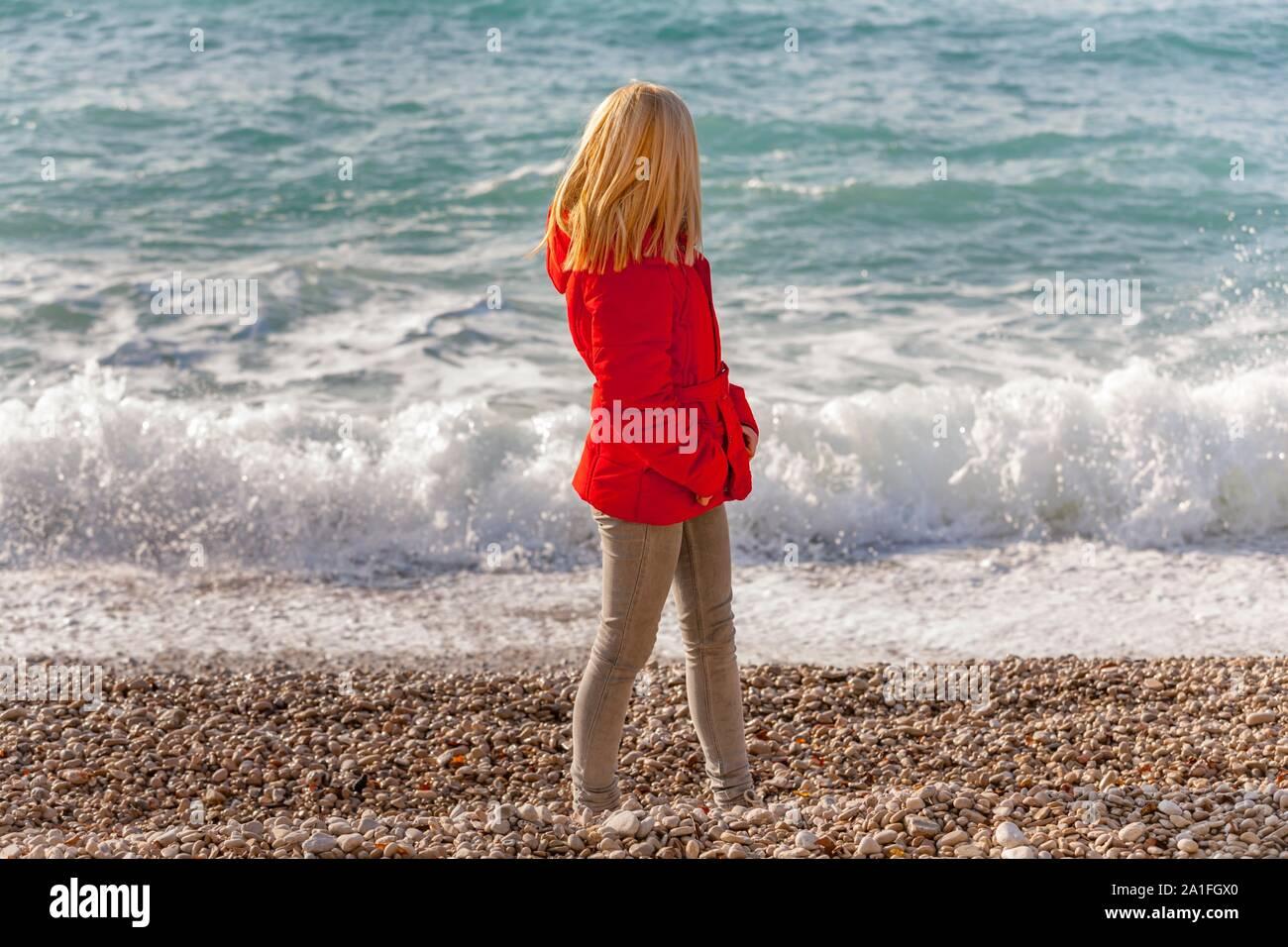 Teen girl blond blonde fair-hair looking away view from back rear behind wearing denim denims pants and Red jacket seaside beach coastline shoreline Stock Photo