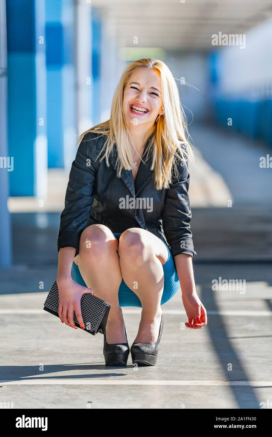 Blonde hair facing frontal view full length whole body female legs heels very happy squatter pleasantly amused amusement Stock Photo