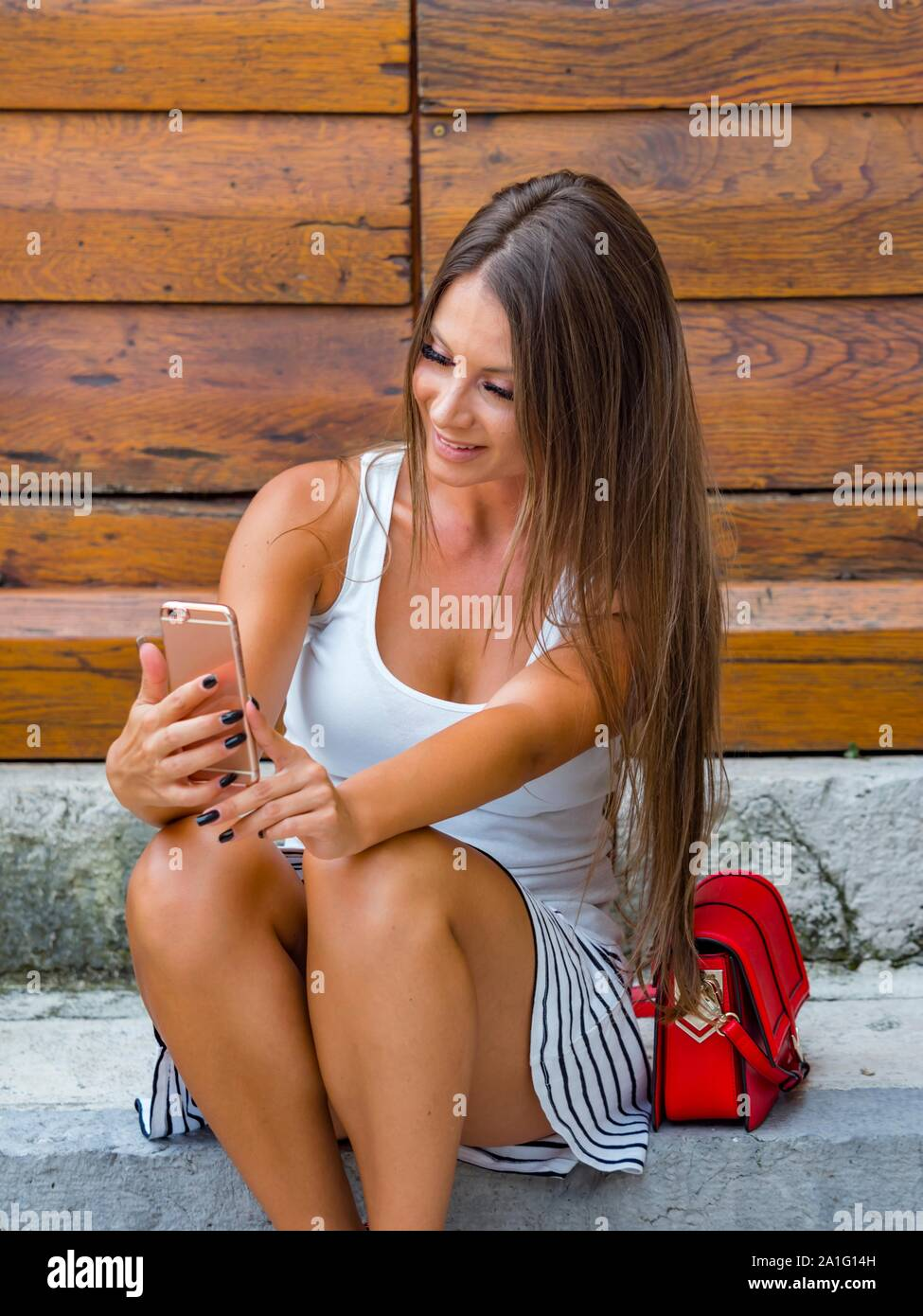 Attractive young woman looking down into camera cellphone making selfie sitting on entrance porch doorstep before wooden doors door Stock Photo