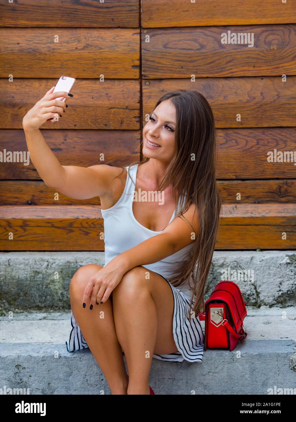 Attractive young woman looking up into camera cellphone sitting on entrance porch doorstep before wooden doors door Stock Photo