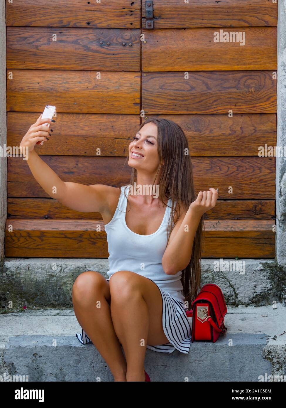 Attractive young woman looking up into camera cellphone sitting on entrance porch doorstep before wooden doors door color vertical Stock Photo