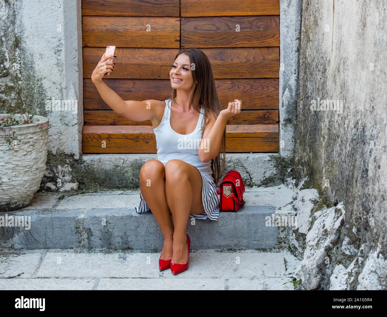Female legs in heels looking up into camera cellphone sitting on entrance porch doorstep before wooden doors door color horizontal highheels Stock Photo