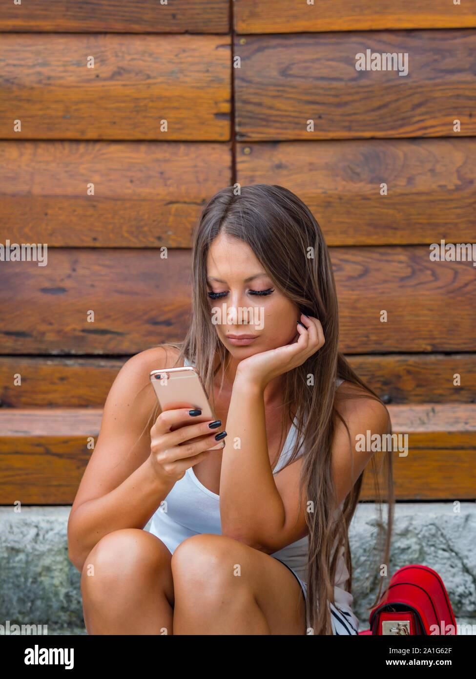 Looking at cellphone smartphone reading facebook sitting on entrance porch doorstep before wooden doors door communicate communicating message Stock Photo