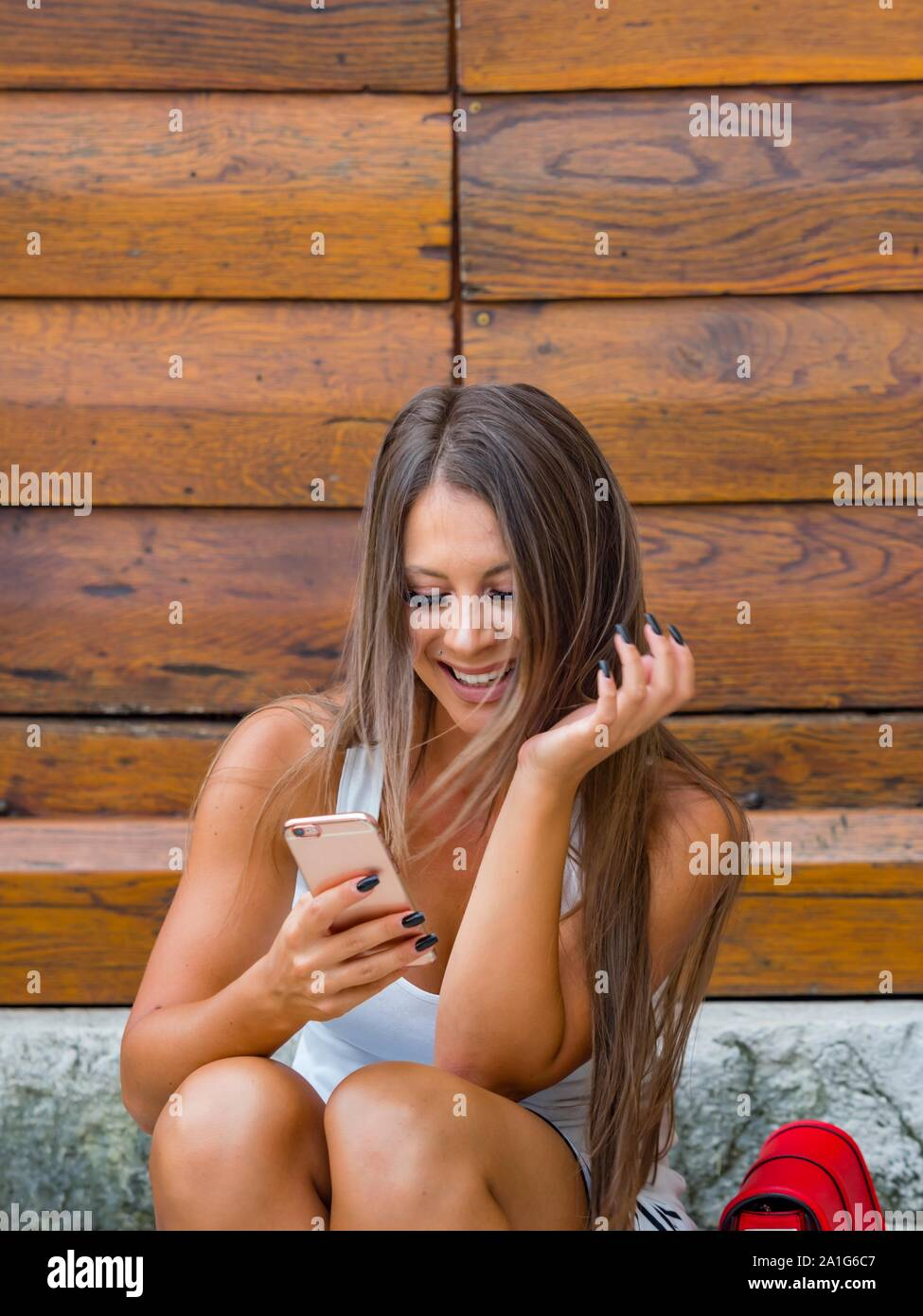 Looking at cellphone smartphone smiling happy reading new facebook inbox messenger message communicate communicating message Stock Photo