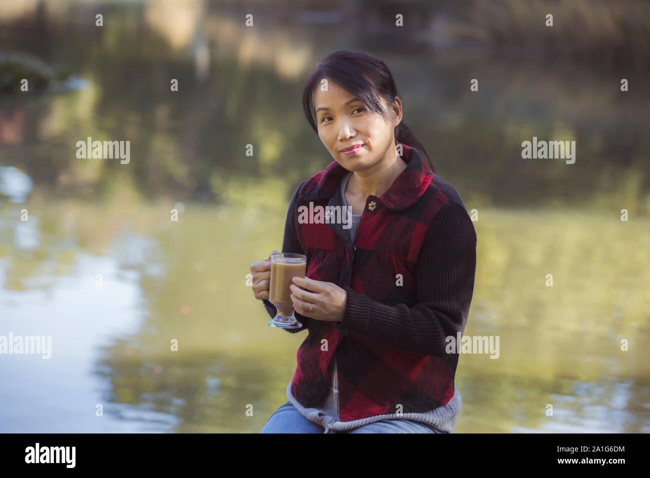 A korean woman enjoys a cup of coffee on a fall day in Spokane, Washington. Stock Photo