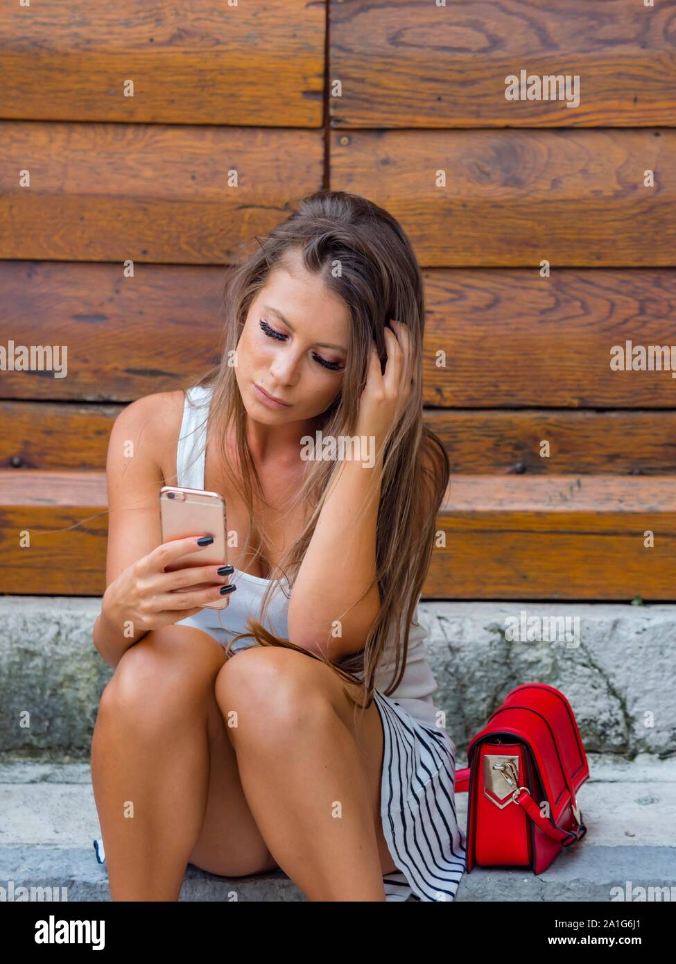 Looking at cellphone smartphone reading facebook sitting on entrance porch doorstep before wooden doors door communicate communicating viber message Stock Photo