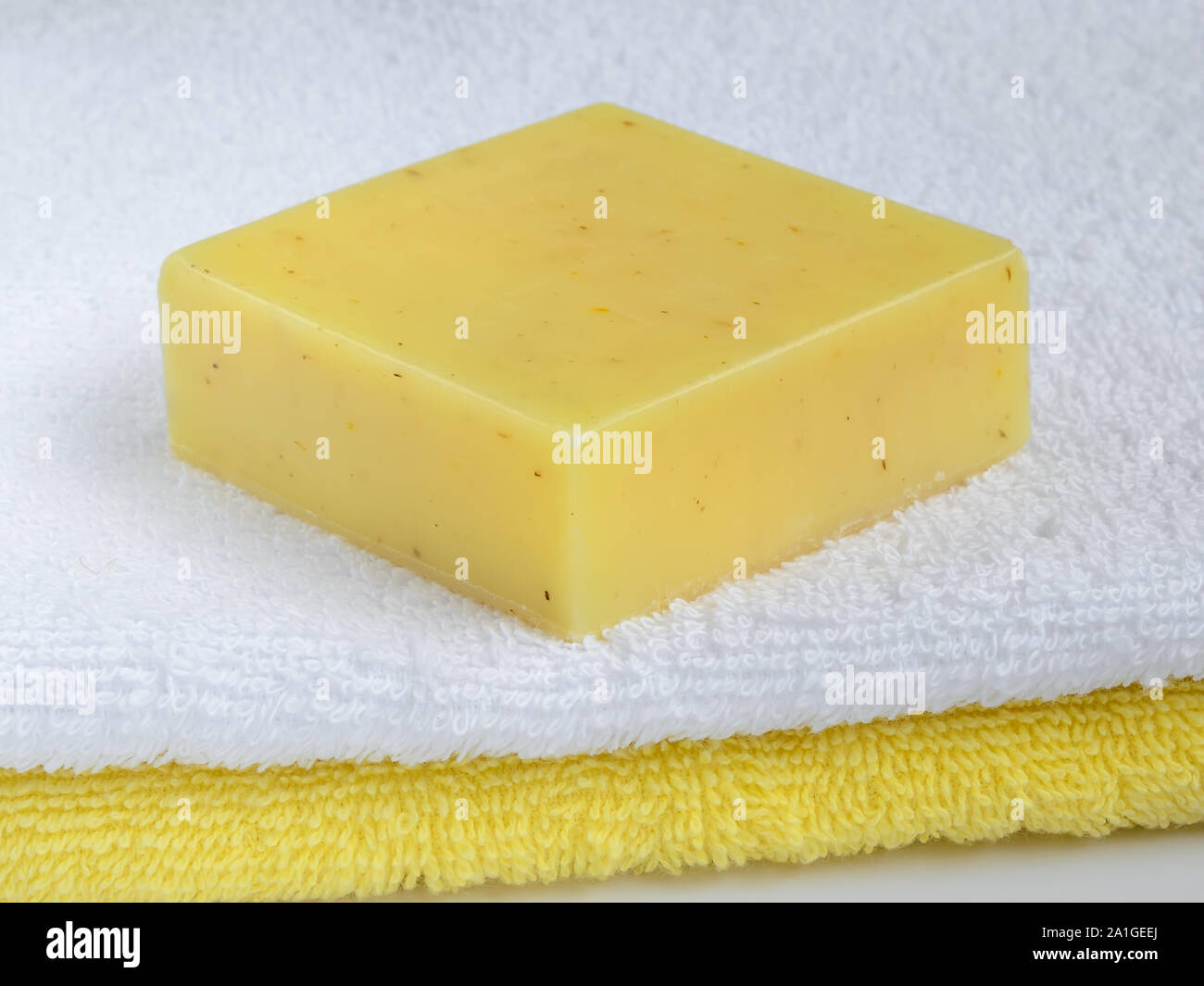 Yellow handmade lemon soap bar on a terry cotton towel. Natural toiletries and hygiene products with herbs and essential oils. Front view. Stock Photo