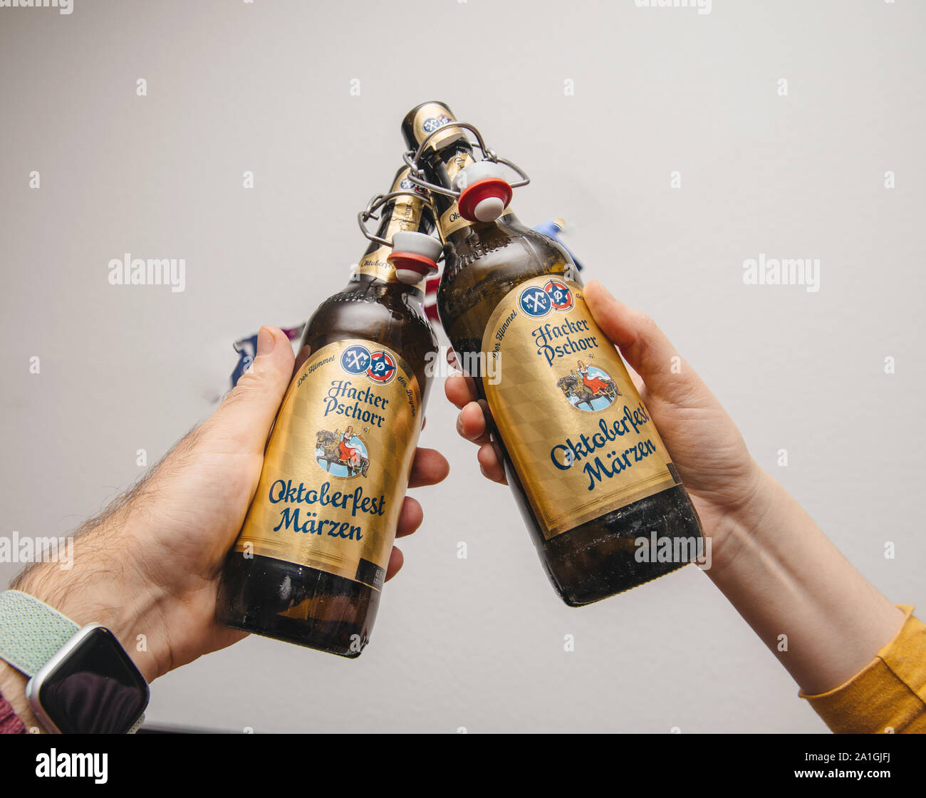 Munich, Germany - Mar 3, 2019: Male hand holding traditional Oktoberfest Marzen Pills beer against white background Stock Photo