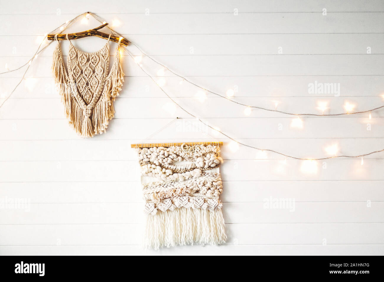 Macrame hanging on white wooden wall with lights. Stylish boho decor, modern wall hanging. Modern interior decor in scandinavian or rustic room. Stock Photo