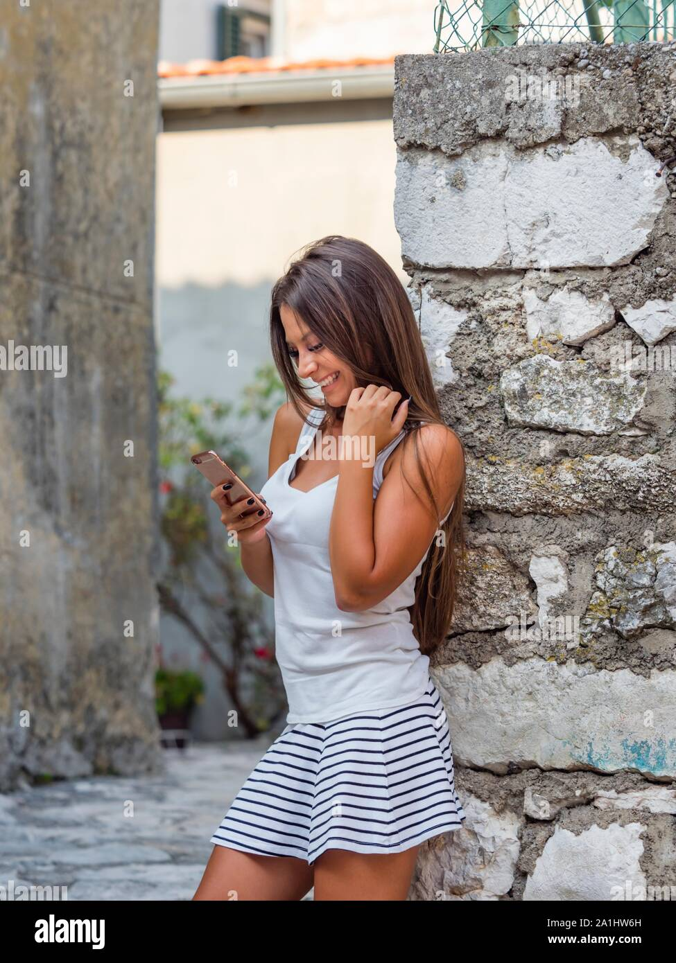 Standing looking at cellphone smartphone smiling happy reading new facebook inbox messenger message communicating message Stock Photo