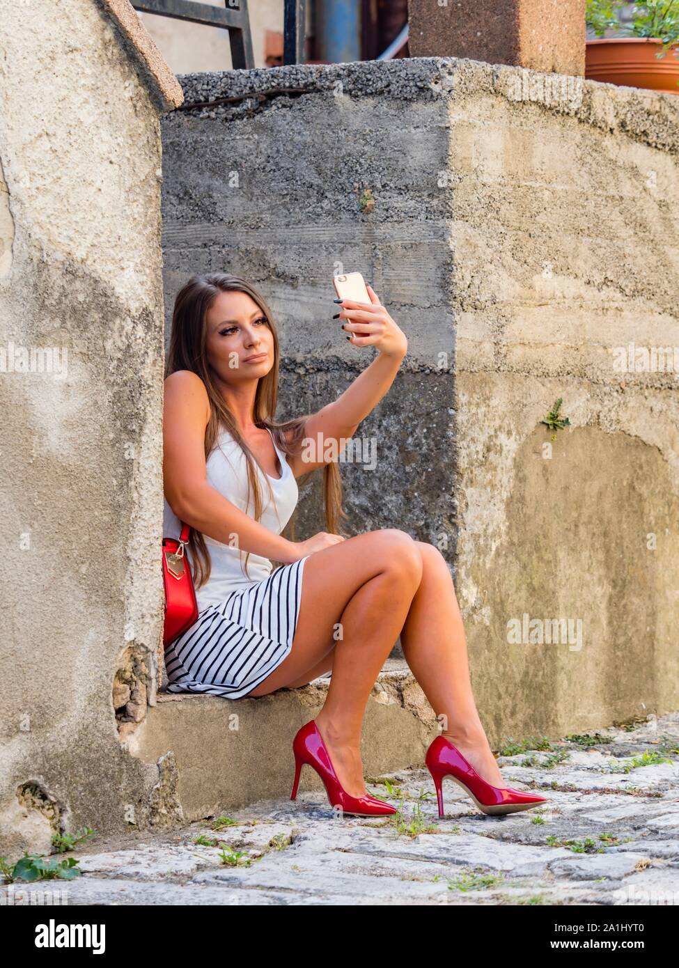 Female legs in heels taking selfie looking up into camera cellphone sitting color vertical Stock Photo