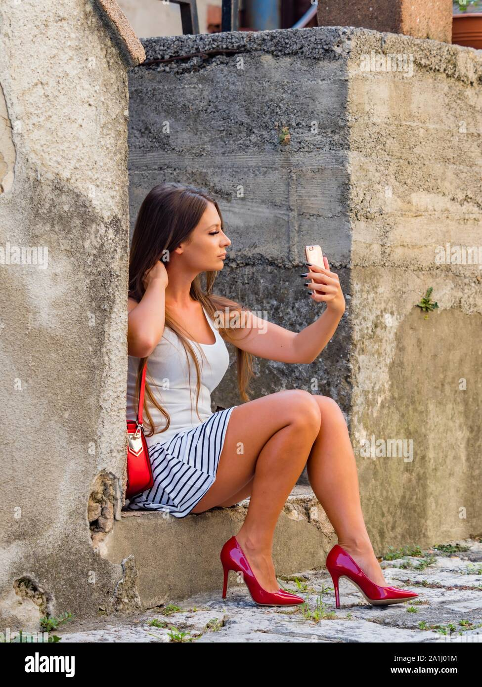 Attractive young woman legs in heels taking selfie looking up into camera cellphone sitting color vertical feminine behavior Stock Photo