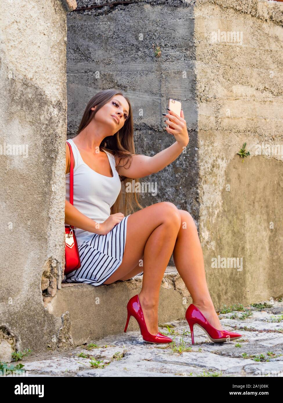 Female legs in Red heels taking selfie looking up into camera cellphone sitting color vertical Stock Photo