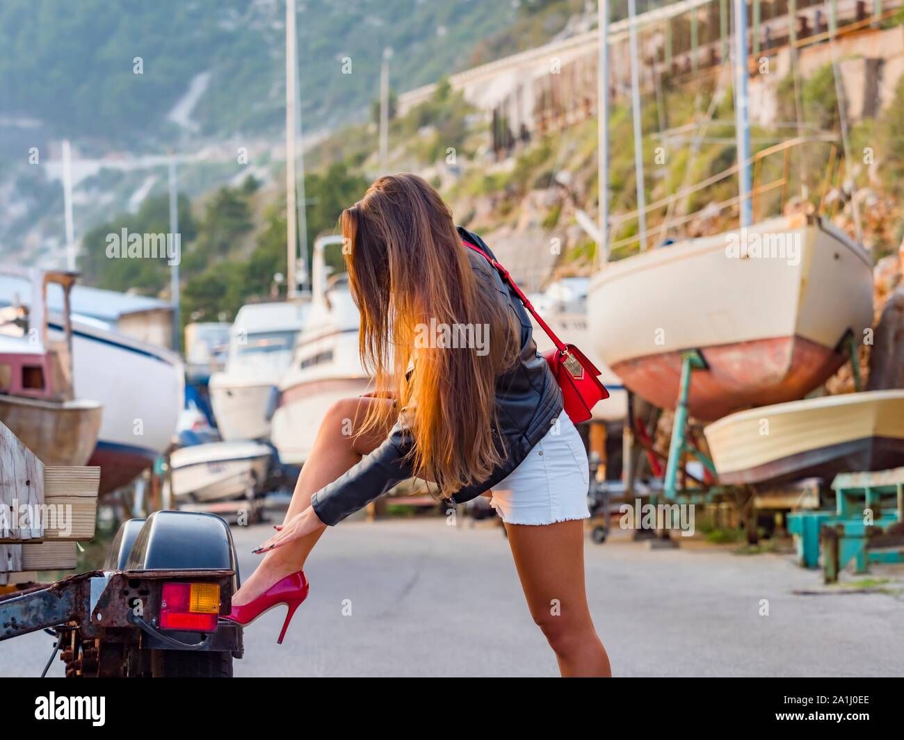 Female admirable leg legs in Red heels wearing White hotpants shorts hot-pants hand touching touch fondle fondling lower leg skin leggy human person Stock Photo
