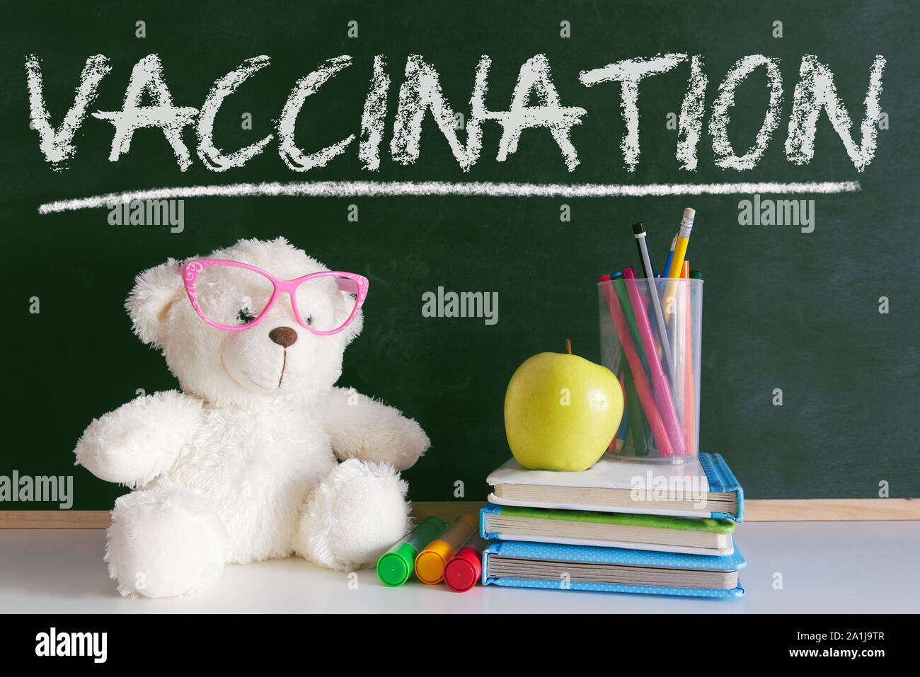 Teddy bear next to a pile of books and an apple in a classroom. Blackboard for the vaccination period concept at school. Stock Photo