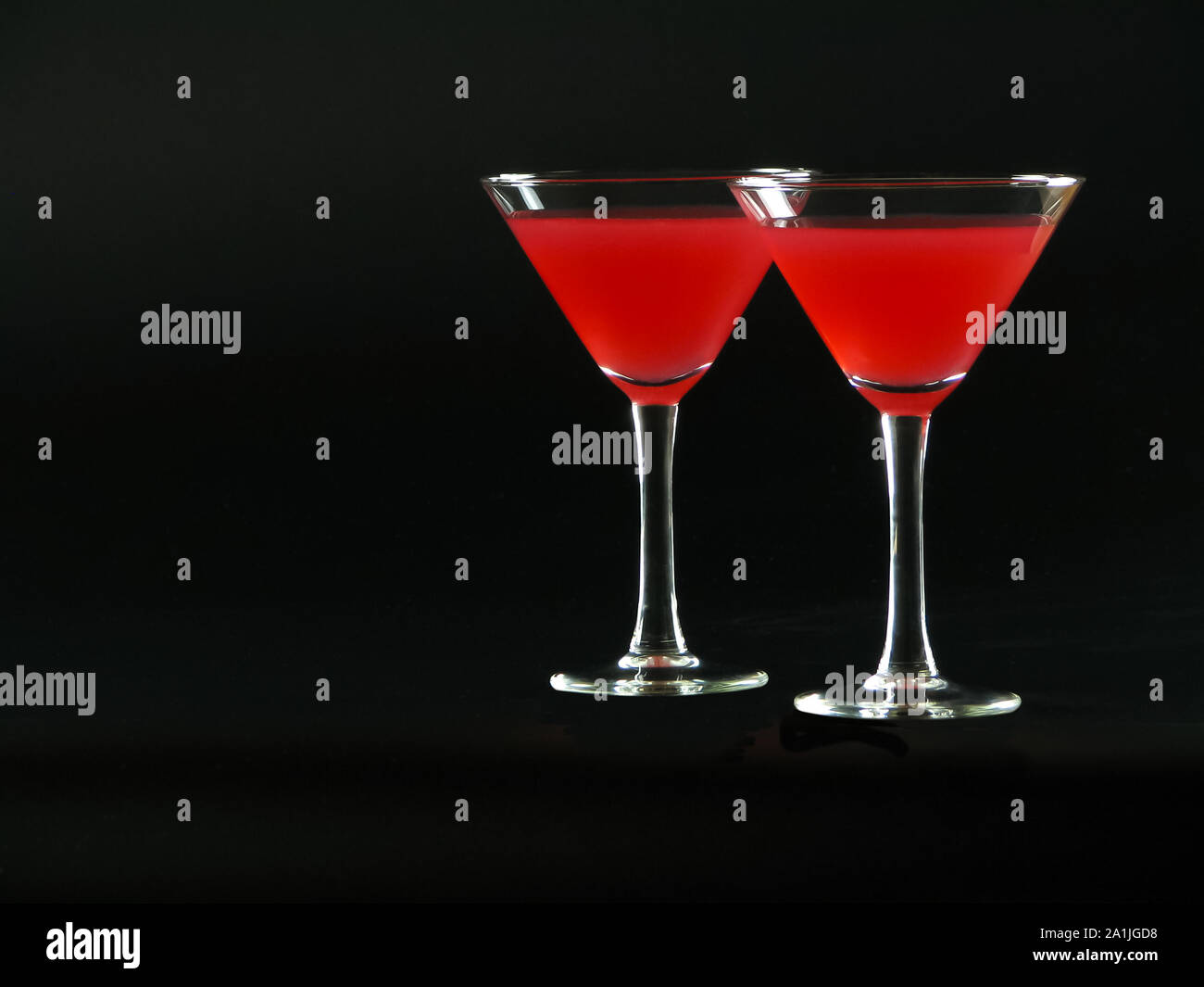Classic Bacardi alcoholic cocktail of bright red color from white rum, lime juice and grenadine, in two conical cocktail glass on a dark background Stock Photo