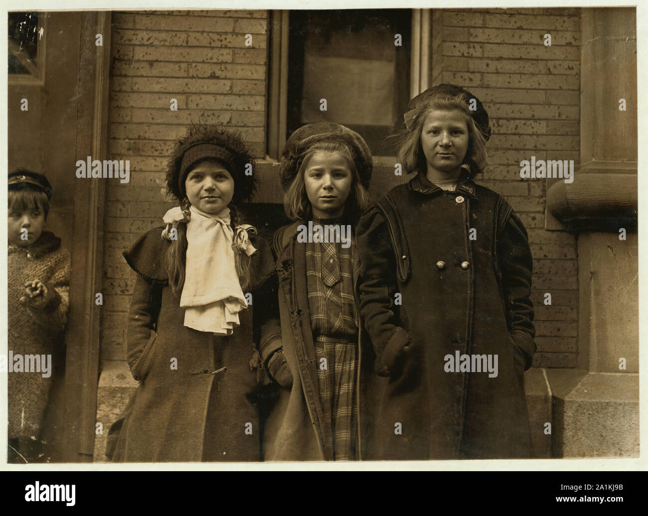Newsgirls waiting for papers. Largest girl, Alice Goldman has been selling for 4 years. Newsdealer says she uses viler language than the newsboys do. Besie Goldman and Bessie Brownstein are 9 years old and have been selling about one year. All sell until 7:00 or 7:30 P.M. daily. Stock Photo