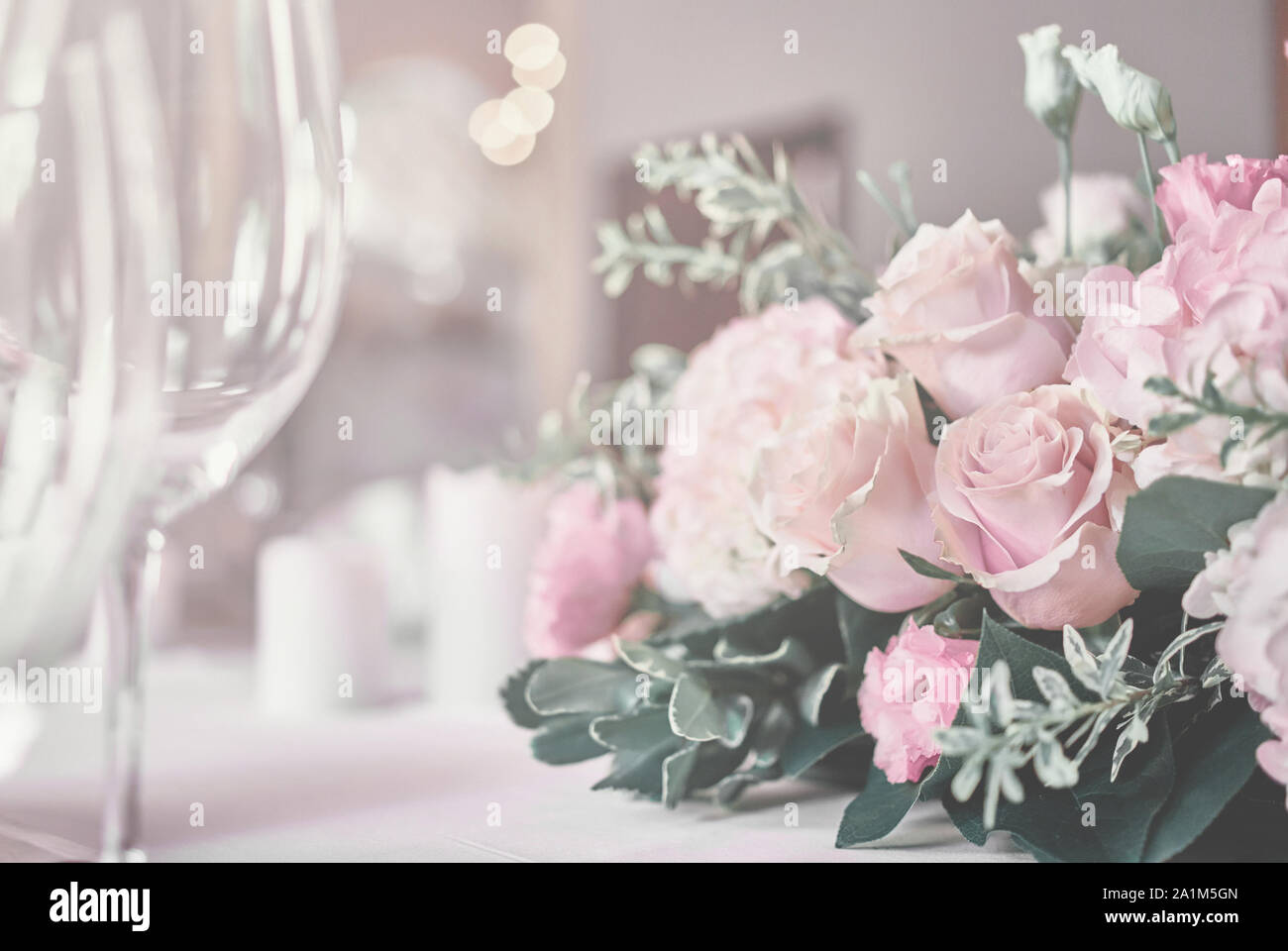 Bouquet on the table. Wine glasses in the foreground. Wedding Banquet or gala dinner. The chairs and table for guests, served with cutlery and crocker Stock Photo